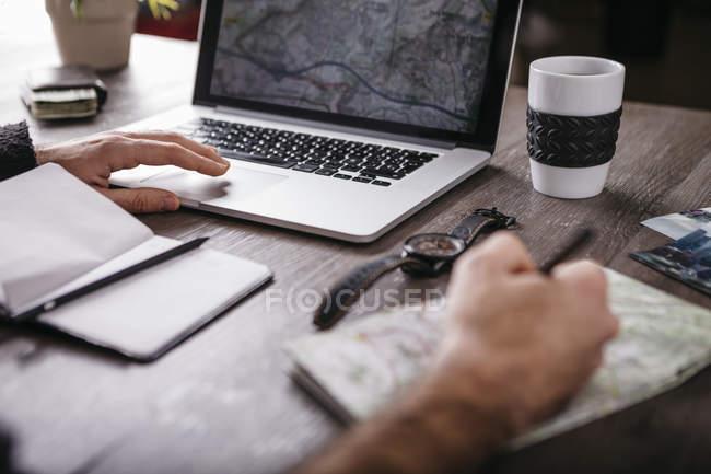 Человек за столом с ноутбуком и карта — стоковое фото