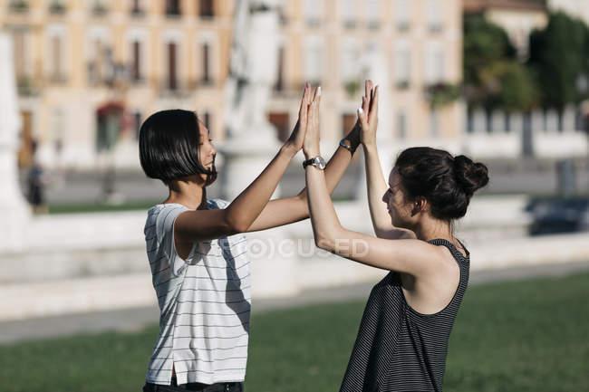 Zwei beste Freundinnen geben hohe fünf im Stadtpark — Stockfoto