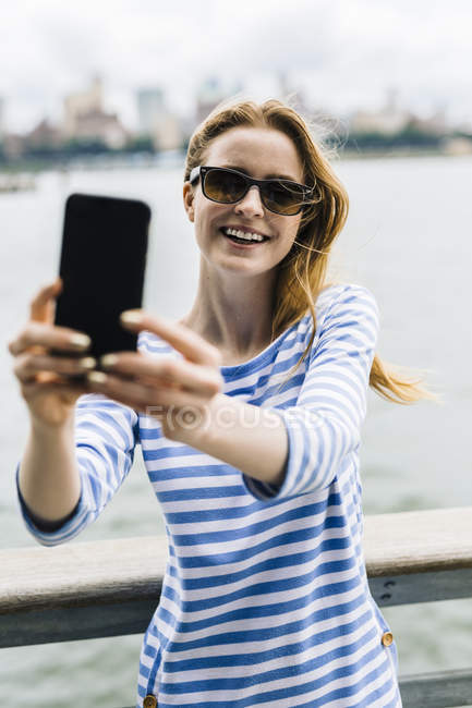 Young woman standing on bridge and taking selfie — Stock Photo
