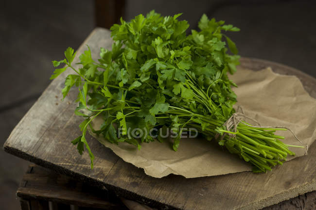 Bunch of fresh parsley on parchment — Stock Photo