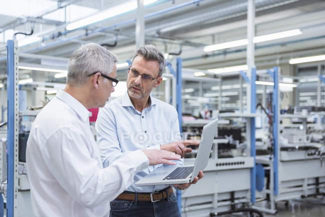 Менеджеры, стоя в фабрике — стоковое фото