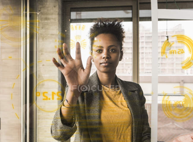 Portrait of young businesswoman touching glass screen — Stock Photo