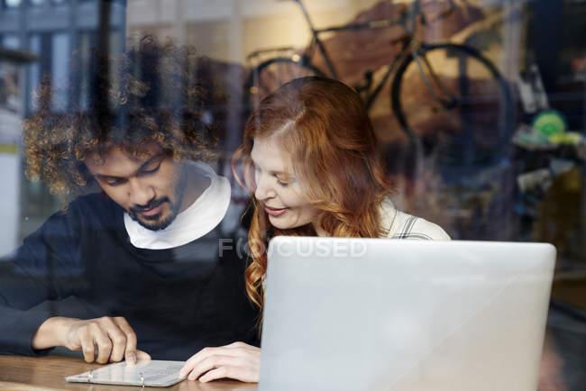 Jeune couple avec ordinateur portable et menu derrière la fenêtre dans le café — Photo de stock