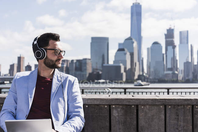 Uomo con cuffie e tablet seduto sul lungomare del New Jersey con vista su Manhattan, USA — Foto stock