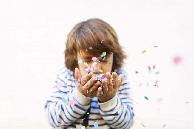 Portrait of boy with closed eyes blowing confetti from hands — Stock Photo