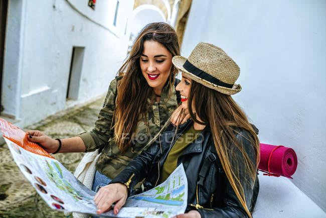 Due donne in viaggio guardando una mappa nella città vecchia — Foto stock