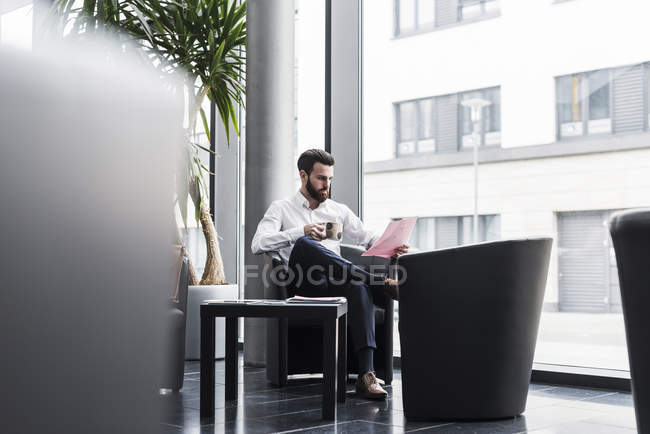 Portrait of young businessman reading documents — Stock Photo