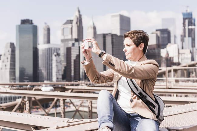 США, Нью-Йорк, Бруклинский мост, пожилая женщина, сидящая на перилах и фотографирующая солнечный городской пейзаж со смартфоном — стоковое фото