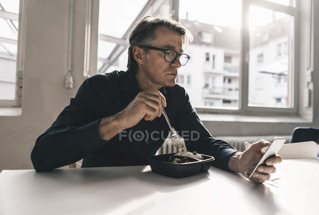 Businessman checking cell phone — Stock Photo