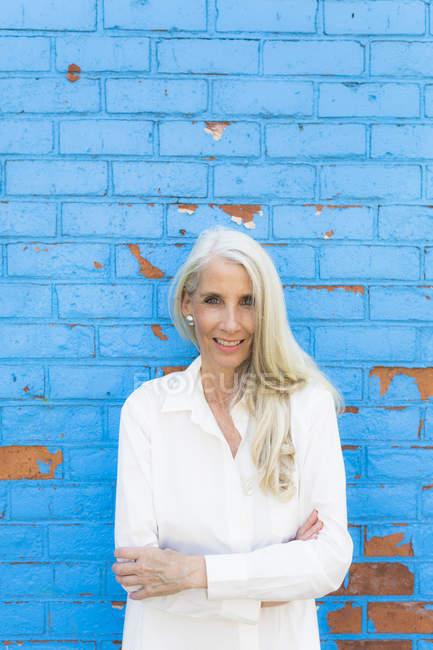 Портрет пожилой женщины, стоящей у кирпичной стены — стоковое фото