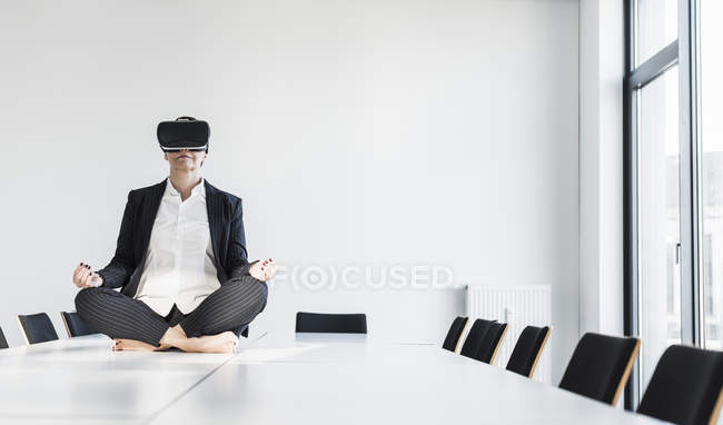 Портрет зрілих бізнес-леді в окулярах віртуальної реальності, сидячи на стіл — стокове фото