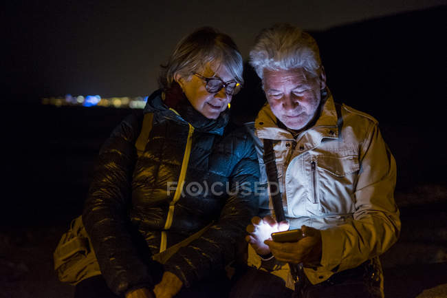 Старшая пара по ночам пользуется мобильным телефоном — стоковое фото
