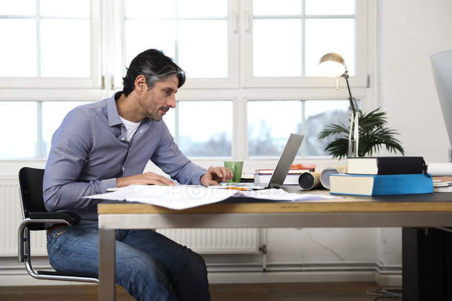 Man using laptop at desk in office — Stock Photo