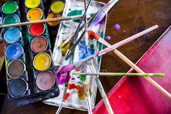 Paint box, brush on canvas at art studio — Stock Photo