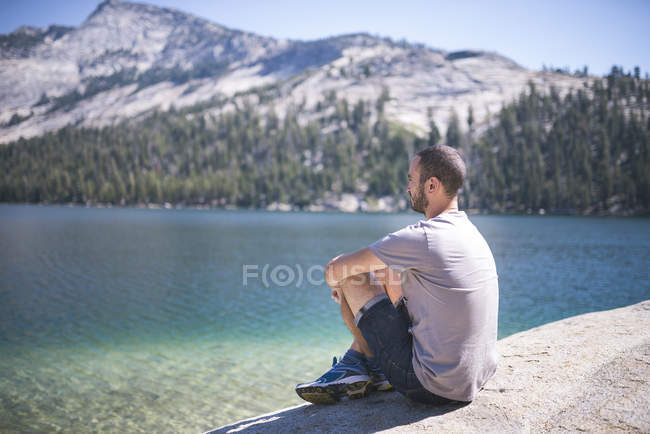 USA, California, Parco Nazionale dello Yosemite, uomo seduto al lago di montagna — Foto stock