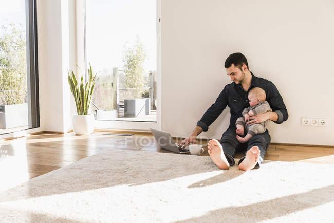 Vater mit Baby am Laptop auf dem Boden sitzend — Stockfoto