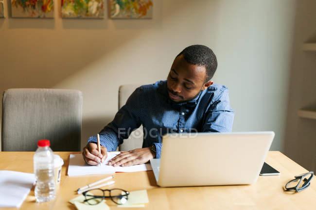 Portrait de jeune homme prenant des notes à la table du bureau — Photo de stock
