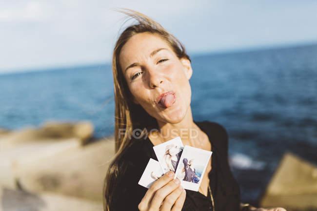 Cheeky giovane donna che mostra foto istantanee di se stessa sul lungomare — Foto stock