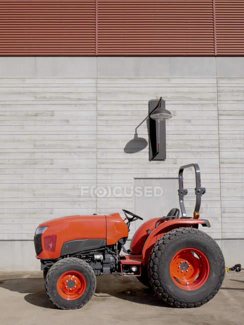 Tractor rojo, estacionamiento en frente de fachada de hormigón - foto de stock