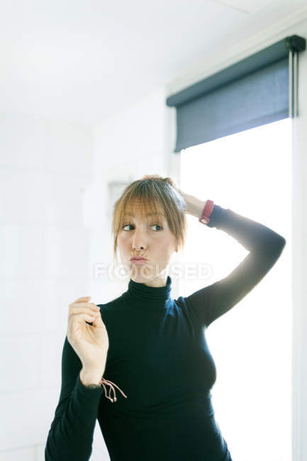 Woman standing next to window and pouting — Stock Photo