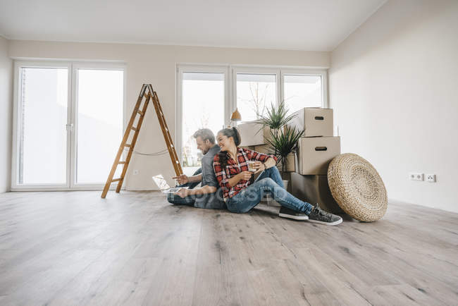 Couple sitting on floor of new home among moving boxes — Stock Photo