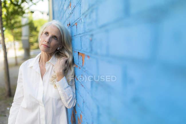 Retrato de mulher sênior de pé perto da parede de tijolo — Fotografia de Stock