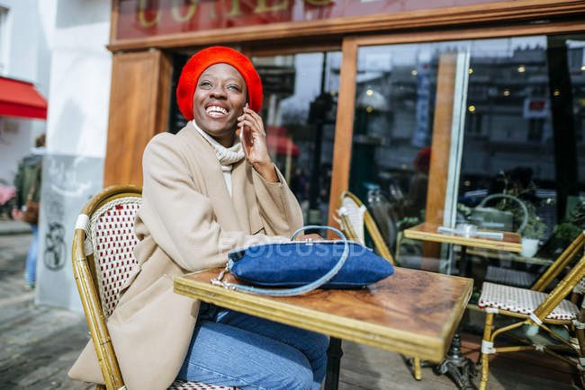 Женщина, сидя в кафе и разговаривает по телефону — стоковое фото