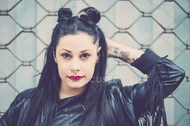 Portrait of dark-haired young woman with black leather jacket and tattoos — Stock Photo