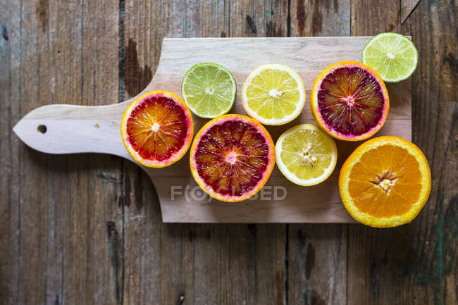 Top view of different fruit halves on chopping board — Stock Photo