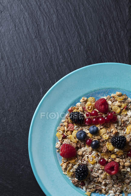 Top view of oat flakes with different berries on blue plate — Stock Photo