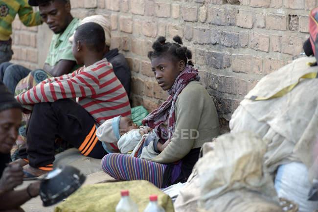 Madagaskar, Fianarantsoa, mãe sem-teto sentada no chão com bebê — Fotografia de Stock