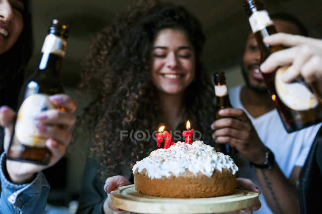 Cropped portrait of young friends with birthday cake and beer — Stock Photo