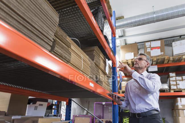 Homme d'affaires permanent dans le hall de l'usine — Photo de stock