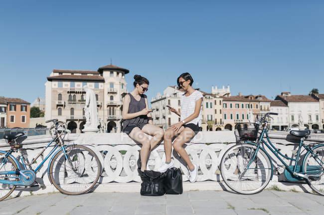Itália, Pádua, dois jovens turistas sentados sobre trilhos e usar telefones celulares — Fotografia de Stock