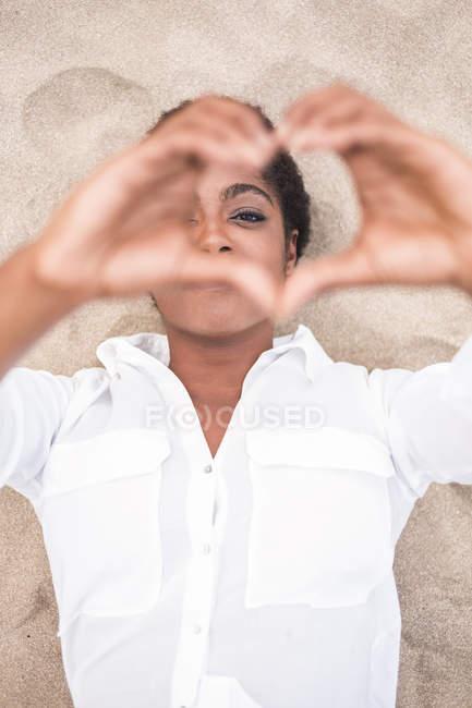 Belle jeune femme black liste coeur de doigts — Photo de stock