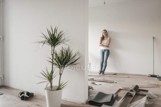 Topfpflanze im neuen Zuhause mit Reife Frau Wand gelehnt, auf Hintergrund — Stockfoto