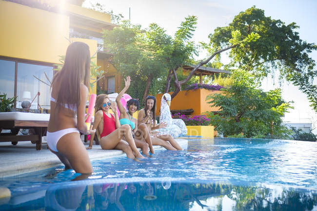 Four young women having fun at the poolside — Stock Photo