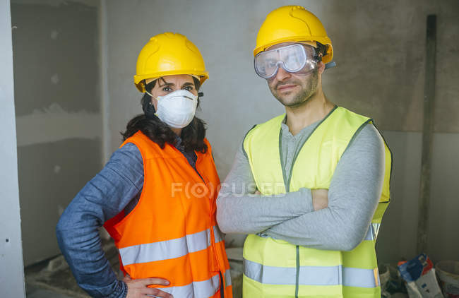 Portrait of working woman with mask and man with safety glasses. — Stock Photo