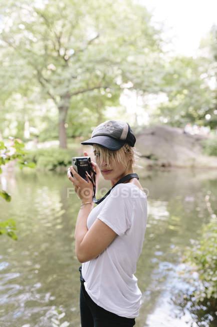 Молода жінка фотографувати на ретро фотоапарат в центральному парку, Манхеттен, Нью-Йорк, США — стокове фото