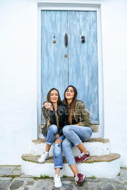 Due giovani donne sorridenti seduti davanti alla vecchia porta blu — Foto stock