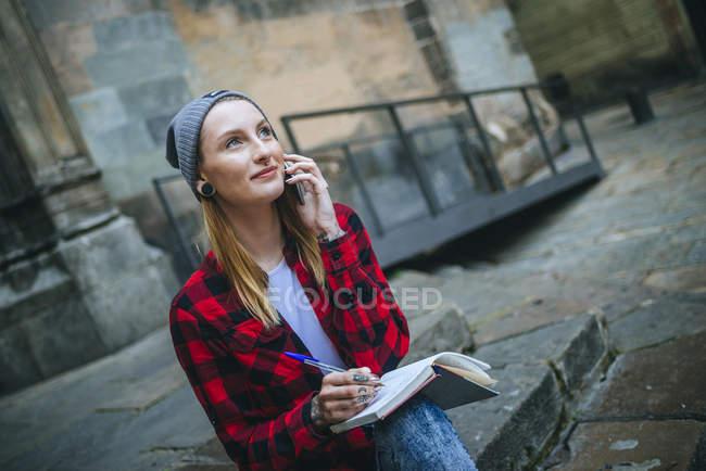 Giovane donna che scrive in un taccuino note del telefono cellulare seduto su una scala all'esterno . — Foto stock