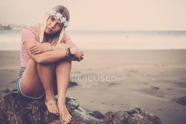 Портрет молодої жінки носять квіти, сидячи на скелі на пляжі — стокове фото