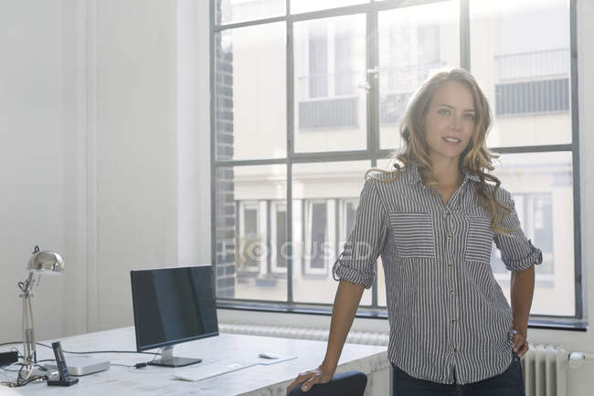 Businesswoman standing in office and looking at camera — Stock Photo