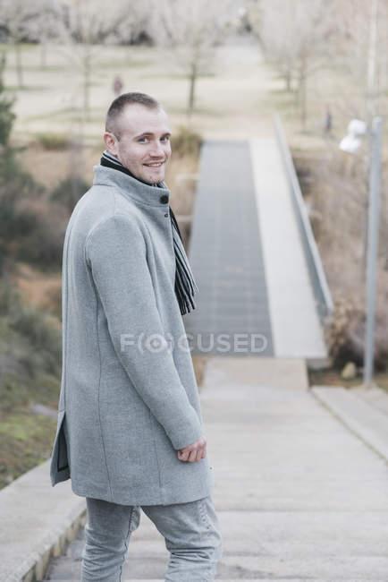 Портрет улыбающегося мужчины на лестнице в парке — стоковое фото