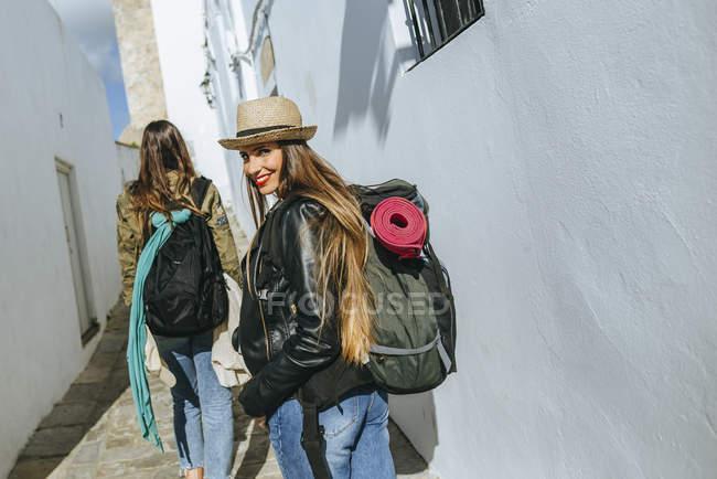 Woman traveling looking at camera while friend walking forward — Stock Photo