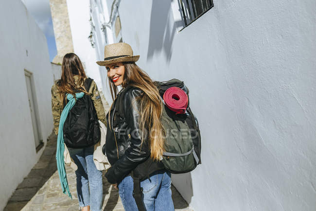 Woman traveling looking at camera while friend walking forward — Stock Photo