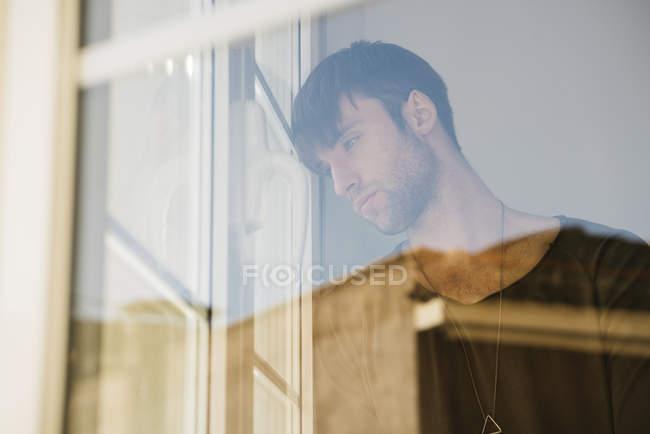 Homem olhando através da janela — Fotografia de Stock