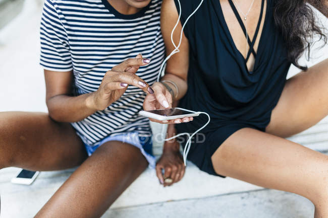 Zwei Freunde, die zusammen mit Kopfhörern und Smartphone auf der Treppe sitzen und Musik hören — Stockfoto
