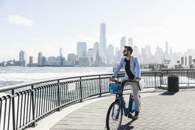 Homme à vélo au bord de l'eau du New Jersey avec vue sur Manhattan, États-Unis — Photo de stock