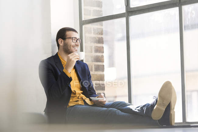 Businessman sitting on window sill and drinking coffee — Stock Photo